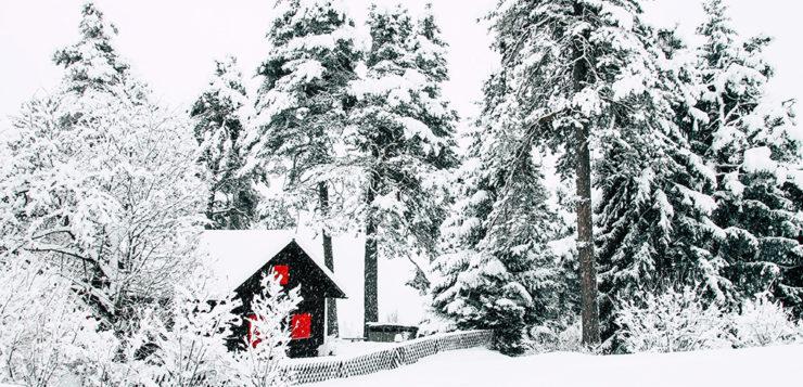 Verschneite Huette mit roten Fenstern