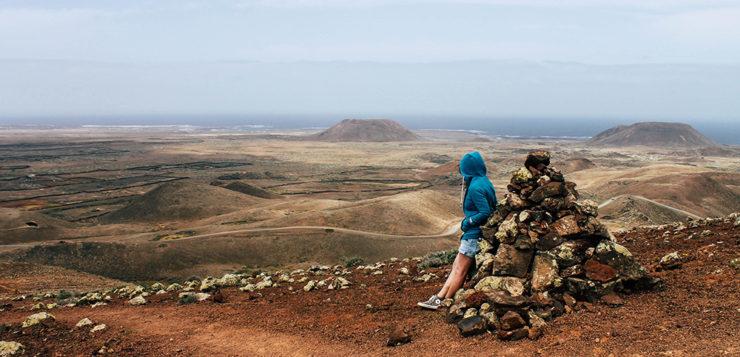 Wanderer blickt ueber Vulkanlandschaft auf Fuerteventura
